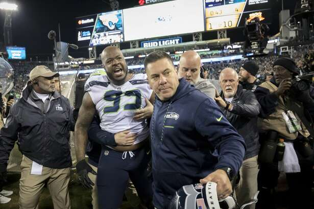 Members of the Seattle Seahawks staff escort Seattle Seahawks defensive tackle Quinton Jefferson (99) from the field after he got into a shouting match with fans, when objects were thrown at him, in the closing moments of an NFL football game against the Jacksonville Jaguars, Sunday, Dec. 10, 2017, in Jacksonville, Fla. Jacksonville won 30-24.(AP Photo/Stephen B. Morton)
