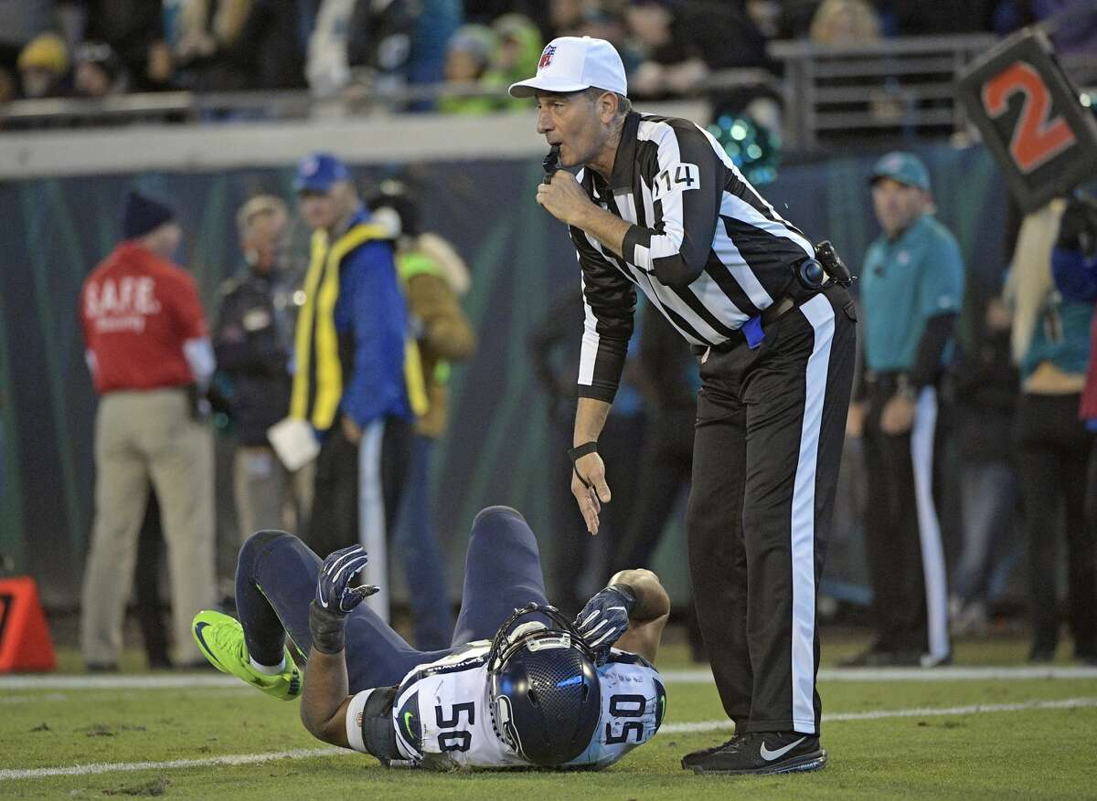 Referee Gene Steratore blows his whistle as he checks on injured player Seattle Seahawks linebacker K.J. Wright (50) during the second half of an NFL football game against the Jacksonville Jaguars, Sunday, Dec. 10, 2017, in Jacksonville, Fla. (AP Photo/Phelan M. Ebenhack)