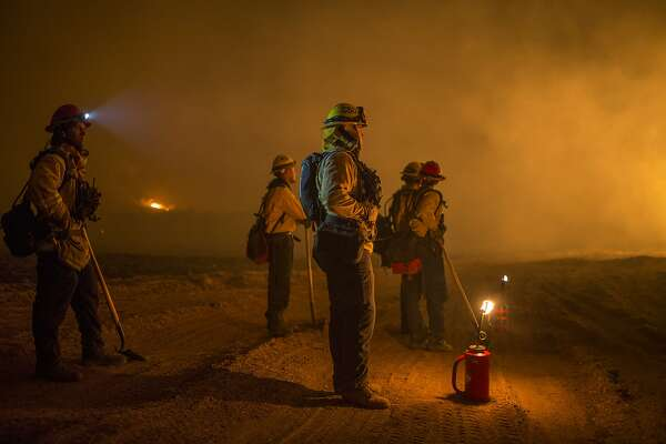 OJAI, CA - DECEMBER 09: Firefighters set a backfire to make progress against the Thomas Fire before the winds return with the daylight near Lake Casitas on December 9, 2017 near Ojai, California. Strong Santa Ana winds have been feeding major wildfires all week, destroying hundreds of houses and forcing tens of thousands of people to stay away from their homes.  (Photo by David McNew/Getty Images)