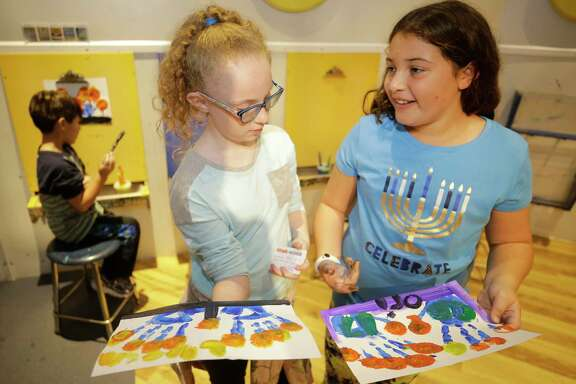 Lyssa Vick, 10, left, and Orina Cohen, 10, compare their finished art work during a Hanukkah activities event lead by the Jewish Community Center at the Children's Museum of Houston.