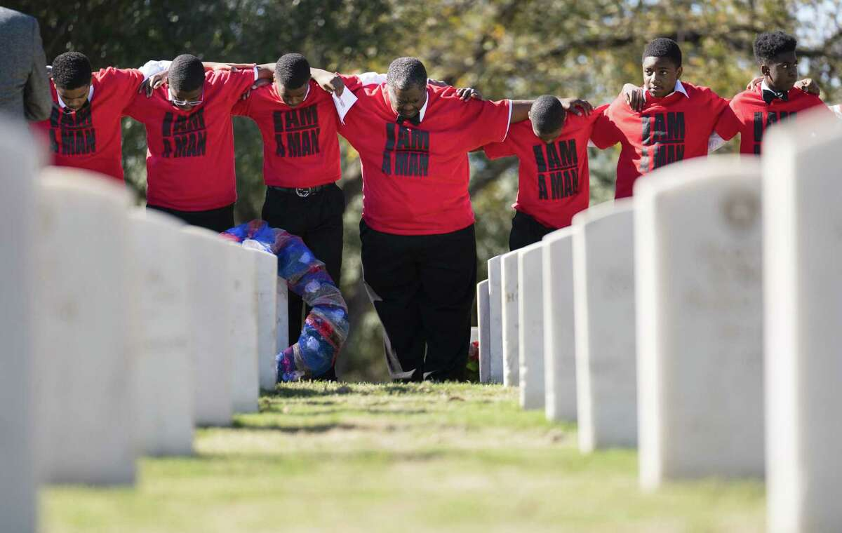 Members of The Bowtie Boys of Dallas and Fort Worth stand Saturday in Fort Sam Houston National Cemetery near the graves of African-American soldiers who were executed in the aftermath of the 1917 Camp Logan Mutiny.
