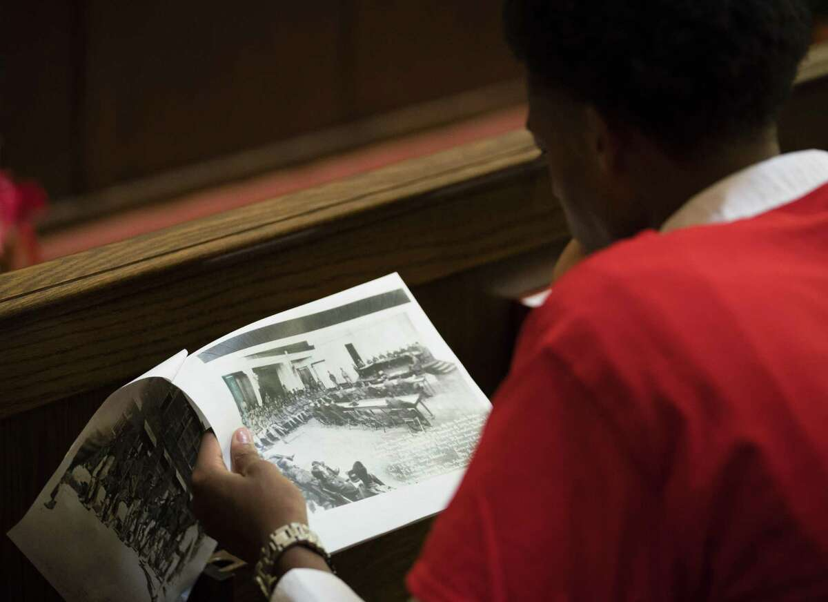 Rahkeesh Robertson sits in Fort Sam's Gift Chapel while looking at a photo that shows the first trial, held at the chapel, for soldiers accused in the mutiny. The executed soldiers were buried in unmarked graves near Salado Creek but were later reburied at the Fort Sam Houston National Cemetery.