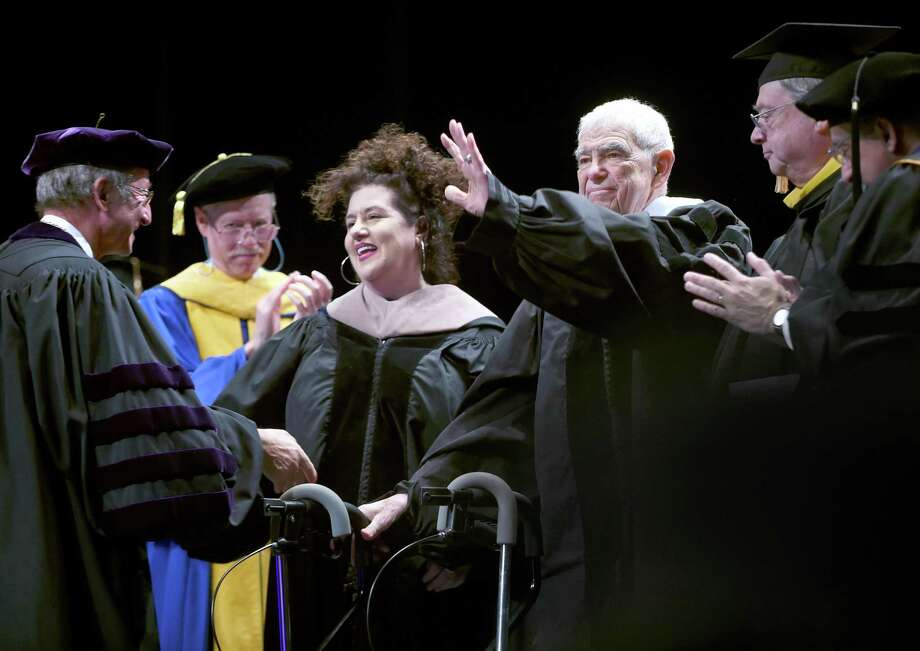 University of New Haven President Steven Kaplan, far left, shakes hands with commencement address speakers Adriana Trigiani, center left, and Bill Persky, waving. Photo: Arnold Gold / Hearst Connecticut Media / New Haven Register