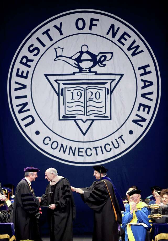 Allen Rosenshine (center), chairman emeritus and retired CEO of BBDO Worldwide, Inc., receives an honorary Doctor of Business Administration at Commencement Exercises for the University of New Haven at the Toyota Presents Oakdale Theatre in Wallingford on December 10, 2017. Photo: Arnold Gold / Hearst Connecticut Media / New Haven Register