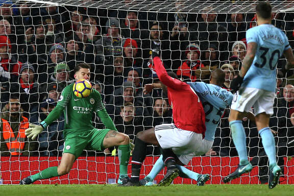 Manchester City goalkeeper Ederson, left, stops a shot from Manchester United's Romelu Lukaku, center, during Sunday's English Premier League showdown at Old Trafford in Manchester, England.