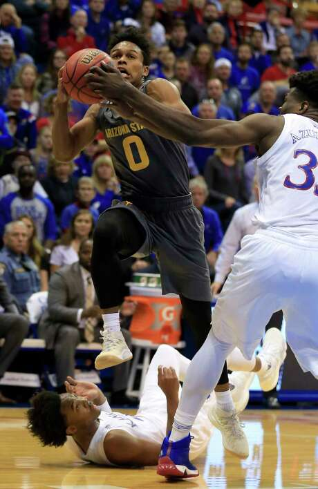 Arizona State guard Tra Holder (0) drives to the basket past Kansas guard Devonte' Graham, bottom, and center Udoka Azubuike, right, during the second half of an NCAA college basketball game in Lawrence, Kan., Sunday, Dec. 10, 2017. Arizona State defeated Kansas 95-85. (AP Photo/Orlin Wagner) Photo: Orlin Wagner, STF / Copyright 2017 The Associated Press. All rights reserved.