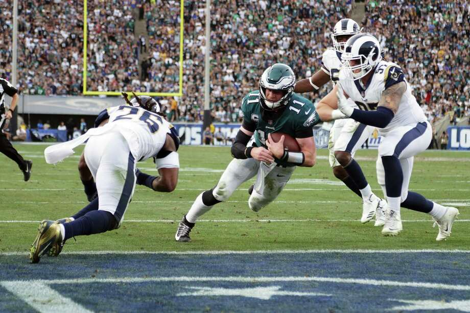 LOS ANGELES, CA - DECEMBER 10:  Carson Wentz #11 of the Philadelphia Eagles is hit by Mark Barron #26 of the Los Angeles Rams during the third quarter of the game.  Wentz was later escorted off the field due to a knee injury at the Los Angeles Memorial Coliseum on December 10, 2017 in Los Angeles, California.  (Photo by Jeff Gross/Getty Images) ORG XMIT: 700070801 Photo: Jeff Gross / 2017 Getty Images