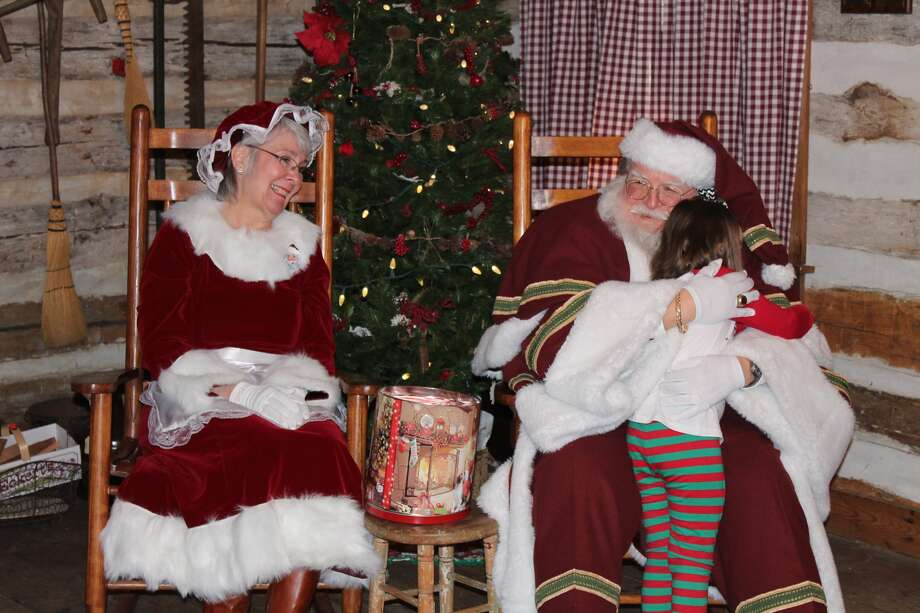 Dozens of youngsters turned out Sunday to visit with Santa and Mrs. Claus at the Yanda Log Cabin in Glen Carbon. The annual open house, at the historic log cabin, includes Christmas-based folk music and sweet treats for the children and their parents. Photo: Bill Tucker • Btucker@edwpub.net