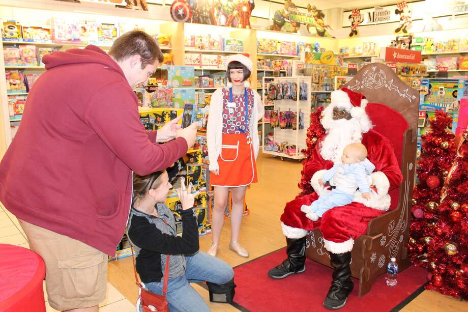 Ryker Wisnasky, 8 months old of Troy, has his picture taken Sunday with Santa Claus in the toy department at Kohl's. In a throw back to the baby boom years, Santa was strategically located in the store during his afternoon appearance. Photo: Bill Tucker • Btucker@edwpub.net