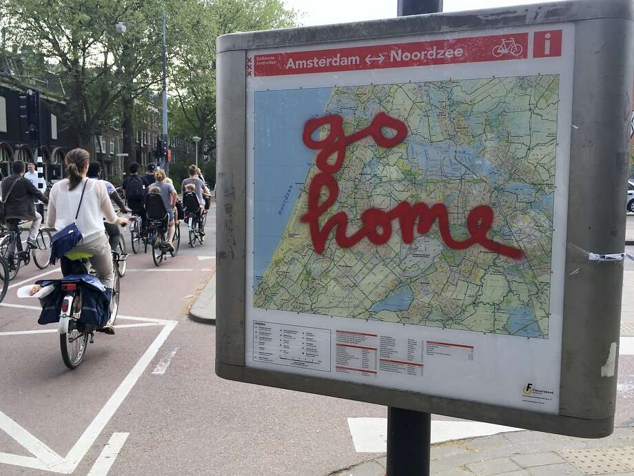 """The graffiti message """"go home"""" covers a map of bicycle paths at Amsterdam's Vondelpark, a popular spot for tourists to ride. Photo: Peter Dejong, Associated Press"""