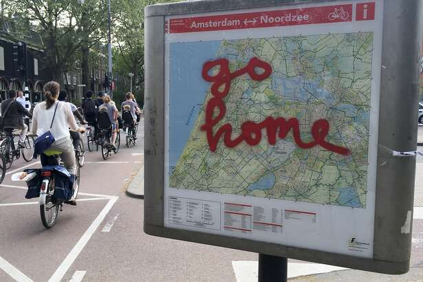 "In this May 11, 2016 photo, graffiti reading ""Go Home"" is sprayed on a map of bicycle paths at the entrance to Amsterdam's Vondelpark, a popular spot for tourists to ride their rental bicycles. ""If the only reason for you to visit Amsterdam is to get loaded, to get stoned out of your mind, look, we can't hold you back from coming, but we don't want you here,"" City alderman Udo Kock said in a recent interview. (AP Photo/Peter Dejong)"
