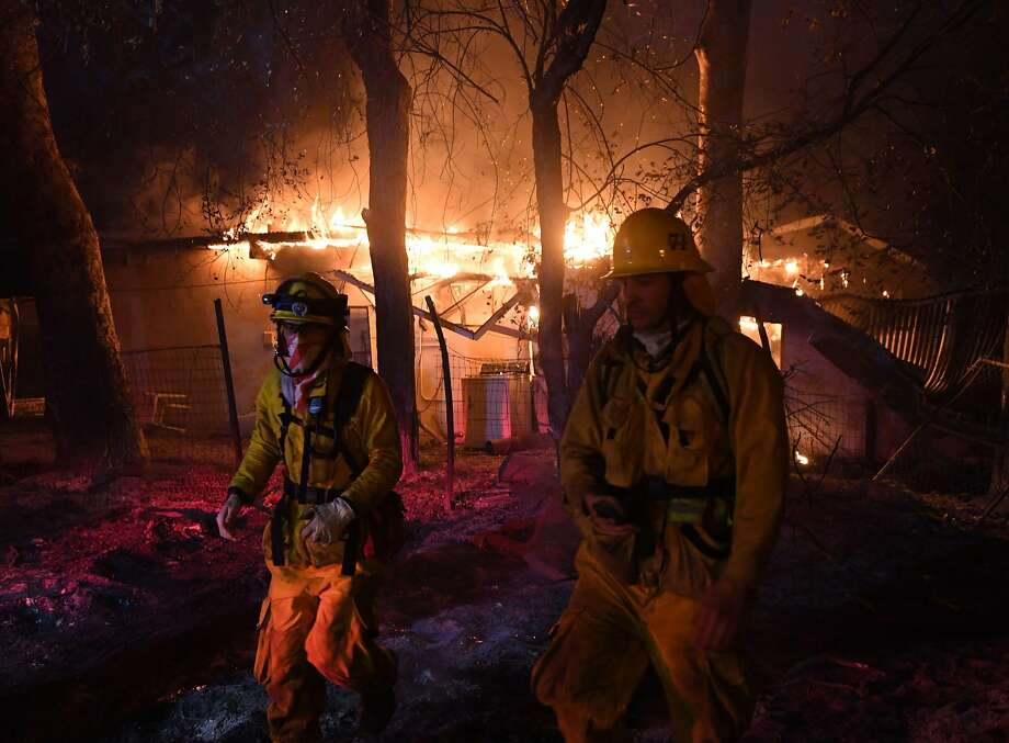 Firefighters move away from a burning house after discovering downed live power lines, as the Thomas wildfire continues to burn in Carpinteria, California, on December 10, 2017. The Thomas fire is only 15 percent contained, now threatening the city of Santa Barbara and the nearby coastal town of Carpinteria, making it one of the worst wildfires in California history. Photo: MARK RALSTON, AFP/Getty Images