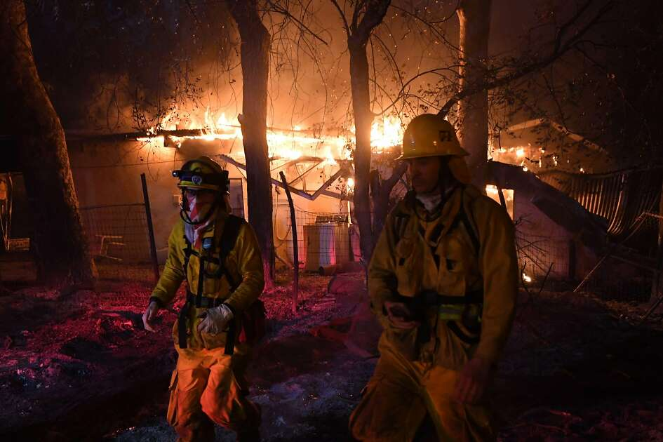 TOPSHOT - Firefighters move away from a burning house after discovering downed live power lines, as the Thomas wildfire continues to burn in Carpinteria, California, on December 10, 2017. The Thomas fire is only 15 percent contained, now threatening the city of Santa Barbara and the nearby coastal town of Carpinteria, making it one of the worst wildfires in California history.  / AFP PHOTO / MARK RALSTONMARK RALSTON/AFP/Getty Images