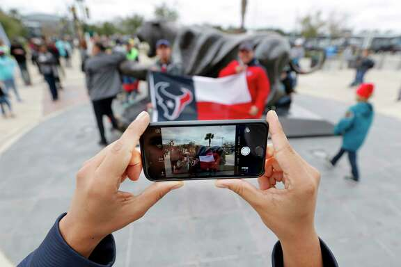 FILE - In this Dec. 7 2014 file photo, Houston Texans fan Erick Salgado takes a photo with his cell phone of  his brother Andres Salgado, left, and his cousin Victor Ticas, right, before the start of an NFL football game against the Jacksonville Jaguars, in Jacksonville, Fla. Yahoo's Flickr and Apple's iCloud Photo Library will automatically transfer photos and videos to your online account, so you get a backup and more space on your device. (AP Photo/Stephen B. Morton, File)