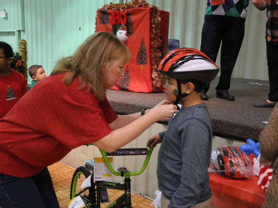 "Christine Cummins with ""Hard Hats for Little Heads"" fits bike winner Emilio Chapa with a helmet at the annual Breakfast with Santa Saturday. Photo: Gail M. Williams"