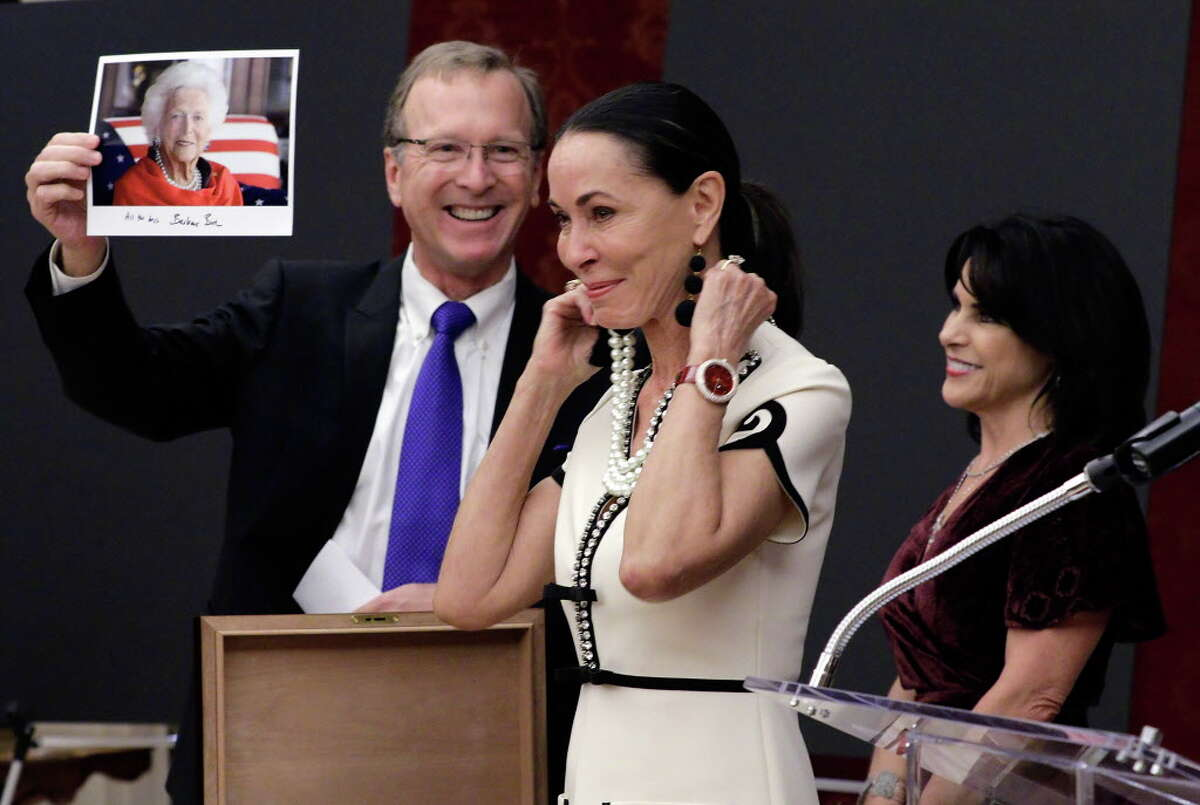 """Neil Bush holds a photo of his mother, former first lady Barbara Bush wearing the same pearl necklace that Sue Smith models that was given to Sue by her husband as Maria Bush looks on at the Barbara Bush Literacy Foundation's """"Celebration of Reading"""" party at the home of Sue and Lester Smith in Houston, TX, Dec. 7, 2017. (Michael Wyke / For the Chronicle)"""