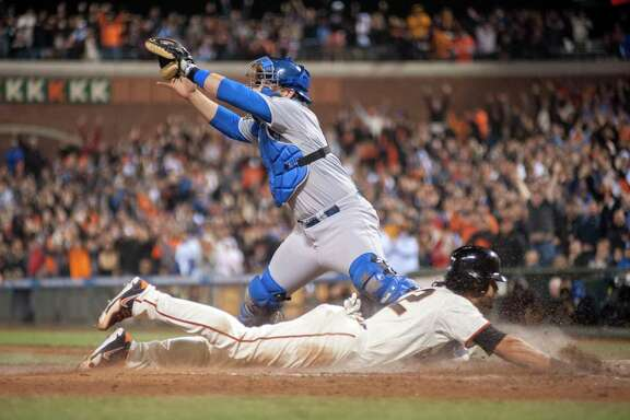 Apr 15, 2014; San Francisco, CA, USA; Los Angeles Dodgers catcher Tim Federowicz looks for the relay throw as San Francisco Giants center fielder Angel Pagan (bottom) slides into home plate during the ninth inning at AT&T Park. Mandatory Credit: Ed Szczepanski-USA TODAY Sports
