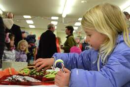 Chandler Drexler, 4, of Darien samples some sweets at Santa's Arrival at Greggs Garden Center & Landscaping, Saturday, Dec. 9, 2017, in New Canaan, Conn.