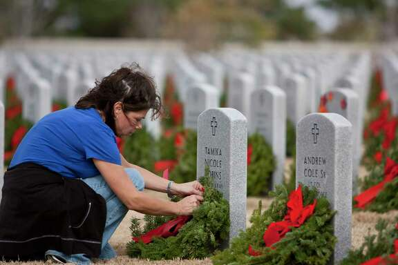 Volunteer Elena Williams of Houston places a wreath on a headstone of a U.S. Army veteran at Houston National Cemetery as part of the Wreaths Across America program.