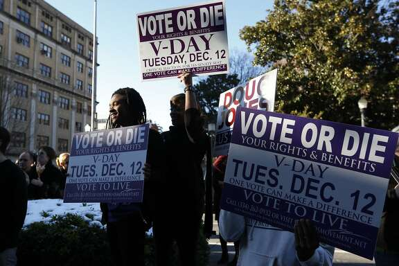 Supporters stand outside encouraging for people to vote after Democratic senatorial candidate Doug Jones spoke at a campaign rally Sunday, Dec. 10, 2017, in Birmingham, Ala. (AP Photo/Brynn Anderson)