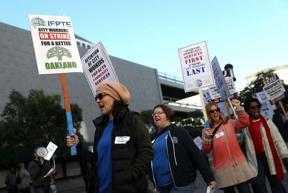 Oakland city workers carry signs as they picket outside a city building on Dec. 5. Photo: Justin Sullivan, Getty Images