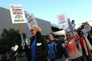 OAKLAND, CA - DECEMBER 05:  Oakland city workers carry signs as they picket outside of a City of Oakland building on December 5, 2017 in Oakland, California. Thousands of Oakland city workers went on strike early Tuesday as contract negotiations stalled out following the expiration of the unionsÕ contract in July.  (Photo by Justin Sullivan/Getty Images)