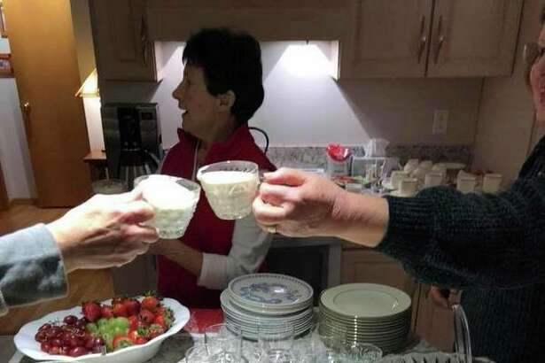 Friends toast with eggnog from a punch bowl at a holiday gathering. (Photo provided)
