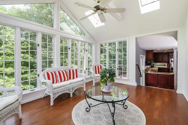 The sun room has three walls of windows, skylights in its cathedral ceiling, and a ceiling fan.
