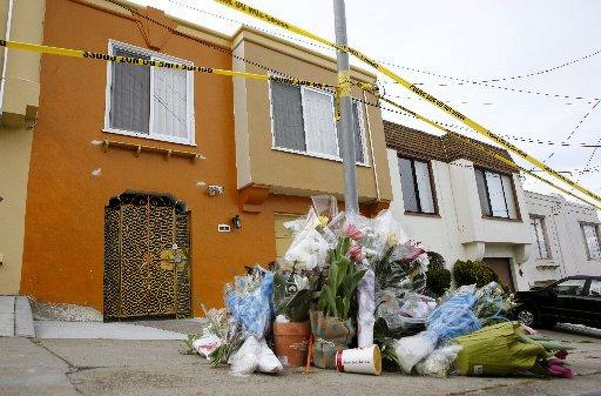 FILE-- A small memorial of flowers lays on the sidewalk outside of a home on Howth Street, the site of a quintuple killing, on Monday, March 26, 2012 in San Francisco.