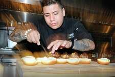 Chef Carlos Baez prepared Kobe beef sliders during the media night preview at The Spread restaurant in Greenwich, Conn., Friday, Dec. 8, 2017. Baez is one of the owners of the restaurant.