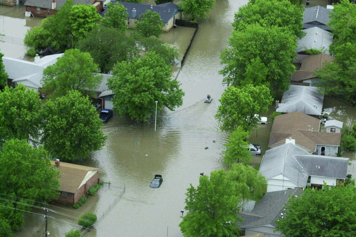 A lone boat maneuvers through flooded streets Saturday, May 6, 2000, in Sand Springs, Okla., after early morning rains swept through several eastern Oklahoma towns, killing a woman, filling some homes with neck-deep water, stranding motorists and shutting down highways.