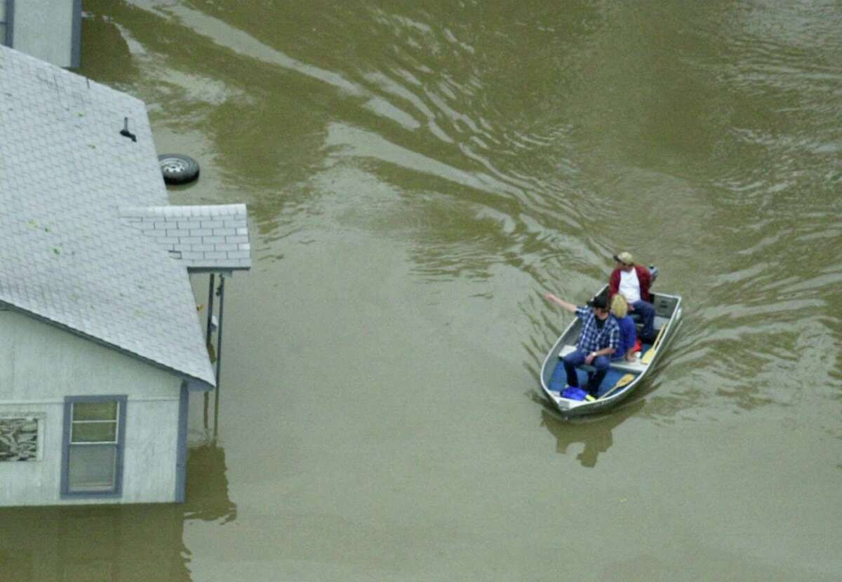 Residents of Sapulpa, Okla. look over flood damage in a boat Saturday, May 6, 2000. Floodwaters swept through several eastern Oklahoma towns Saturday, killing a woman, filling some homes with neck-deep water, stranding motorists and shutting down highways.