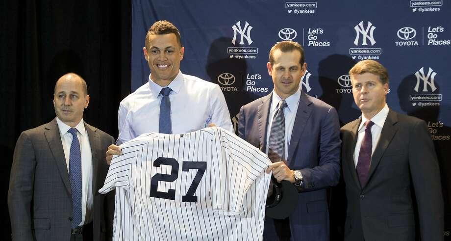 Yankees General Manager Brian Cashman, left, stands next to new Yankee Giancarlo Stanton, center, and his new jersey with Yankee Manager Aaron Boone, right middle, and Yankee Owner Hal Steinbrenner, right, during the Major League Baseball winter meetings in Orlando, Fla., Monday, Dec. 11, 2017. (AP Photo/Willie J. Allen Jr.) Photo: Willie J. Allen Jr., Associated Press