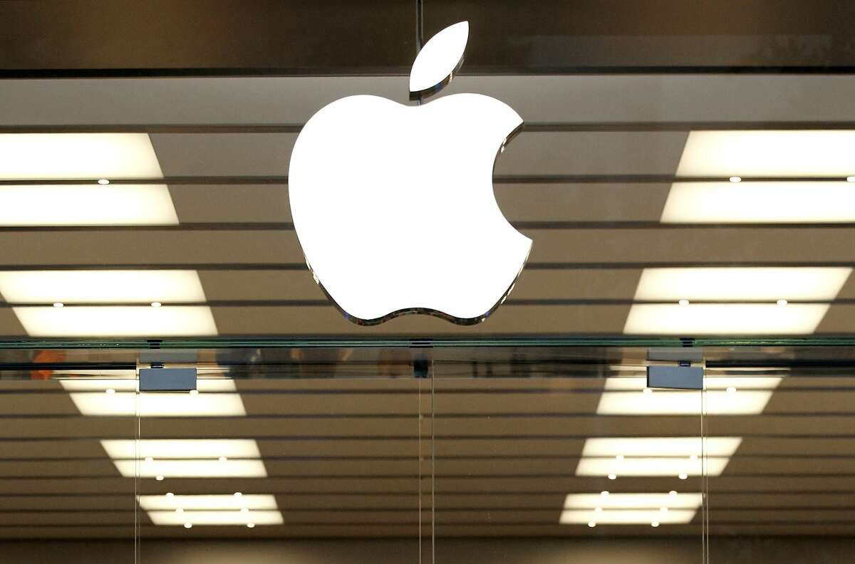 This Thursday, Sept. 19, 2013, file photo shows the Apple logo above a store location entrance in Dallas. Roughly 50 people were forced to evacuate a Zurich Apple Store Tuesday, Jan. 9, 2017, after an iPhone battery overheated, police said.