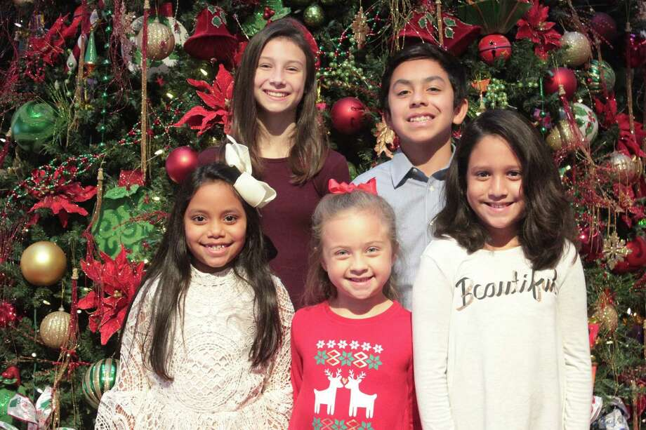 """Elena Vazquez, 13, of Friendswood, second from left, is savoring her role as Fan, Ebeneezer Scrooge's sister, in Alley Theatre's production of """"A Christmas Carol - A Ghost Story of Christmas."""" """"I get to sing 'Barbara Allen,' a traditional English song,"""" the Friendswood Junior High School eighth-grader says. Her sister, Ava, 13, right, plays several roles in the show. Other local youths in the play are Ariel Molina, 7, of Pasadena, left, Camille Hutchison, 6, of Pasadena and Ayden Molina, 12, of Pasadena."""