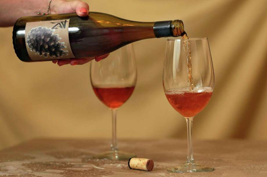 This Tuesday, Oct. 10, 2017, photo shows orange wine, a Salinia Wine Company 2012 Sonoma County Chalk Hill Pinot Gris, in New York. The unique amber-colored wine is creating a buzz in an industry long dominated by shades of red, white and rose. The orange color comes not from citrus fruit, but by fermenting white wine grapes with their skins on before pressing, a practice that mirrors the way red wines are made. (AP Photo/Richard Drew) Photo: Richard Drew, STF / AP