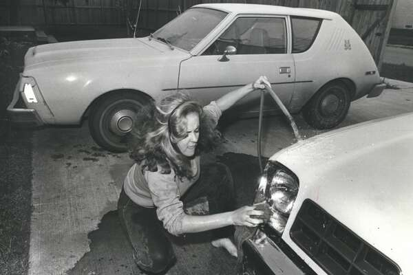 Montrose-area resident Mary Long hoses down her car in 1982 to rid it of volcanic ash that drifted to Houston from a recent eruption of El Chichon volcano about 420 miles southeast of Mexico City. The ash blanketed the Houston area and hampered traffic in coastal airports. A cold front that moved into the area Friday was expected to push the ash cloud toward the Gulf of Mexico.