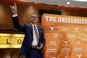 Chris Del Conte holds up the Hook'em sign at a news conference where he was introduced at the new vice president and athletics director for the University of Texas, Monday, Dec. 11, 2017, in Austin, Texas.