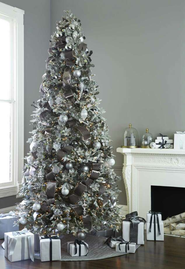 A flocked Balsalm Hill tree sparkles when adorned with ornaments in shades of pewter and silver.