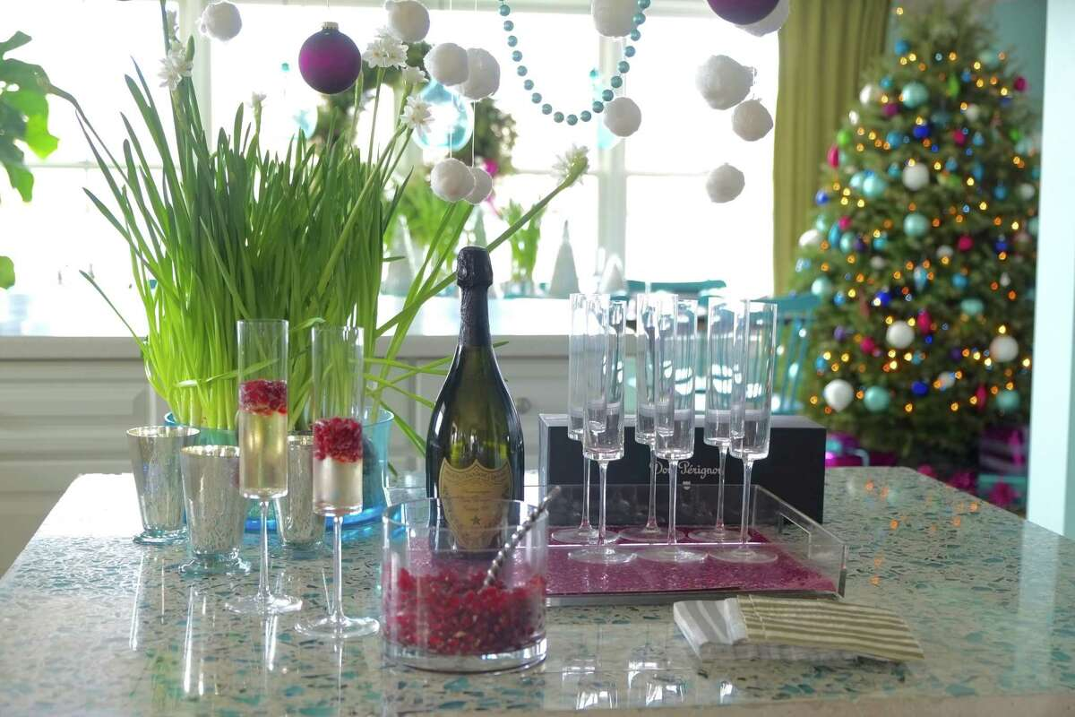 This undated photo provided by Massachusetts-based interior designer Kristina Crestin shows a table setup by Crestin. To bring a subtle sparkle to holiday entertaining, Crestin added a few mercury glass votive holders and a cluster of paperwhite plants in silver-toned metal pots to a champagne bar, and included sheets of metallic paper in a tray beneath the champagne glasses. (Kristina Crestin via AP)
