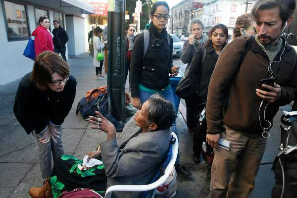 Anne Gallagher (left) visits with Alice, a homeless woman who spends her days and nights in front of the Burger King at 16th and Mission streets, as commuters board a shuttle bus in San Francisco, Calif. on Wednesday, Nov. 29, 2017.