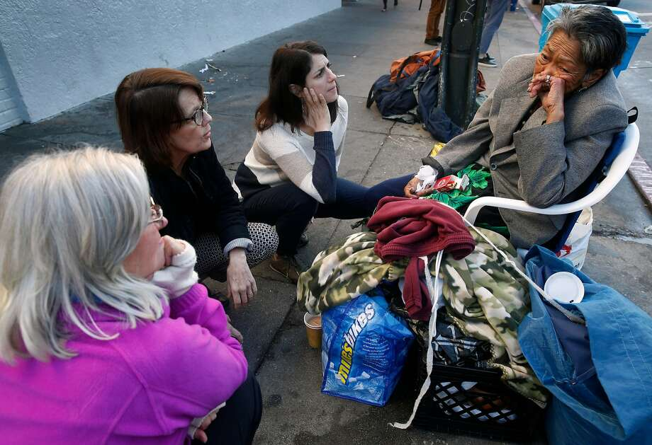 From left, Rory Ryan, Anne Gallagher and Supervisor Hillary Ronen visit with Alice, a homeless woman who spends her days and nights in front of the Burger King at 16th and Mission streets, in San Francisco, Calif. on Wednesday, Nov. 29, 2017. Photo: Paul Chinn, The Chronicle