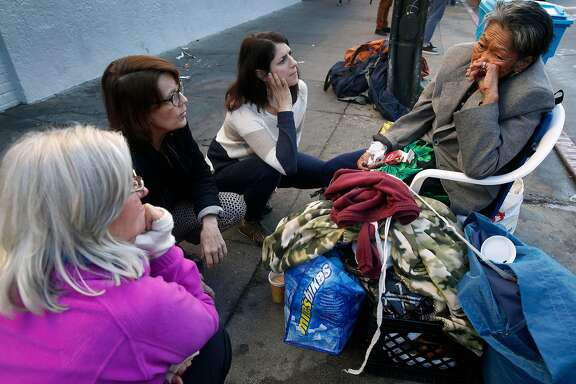 From left, Rory Ryan, Anne Gallagher and Supervisor Hillary Ronen visit with Alice, a homeless woman who spends her days and nights in front of the Burger King at 16th and Mission streets, in San Francisco, Calif. on Wednesday, Nov. 29, 2017.