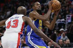 Golden State Warriors forward Kevin Durant (35) takes a shot against Detroit Pistons forward Anthony Tolliver (43) during the second quarter of an NBA basketball game Friday, Dec. 8, 2017, in Detroit. (AP Photo/Duane Burleson)