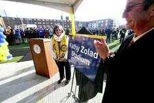 Kathy Zolad (left) and University of New Haven President Steven Kaplan unveil a nameplate for the stadium being named in honor of Zolad at the university in West Haven Monday.