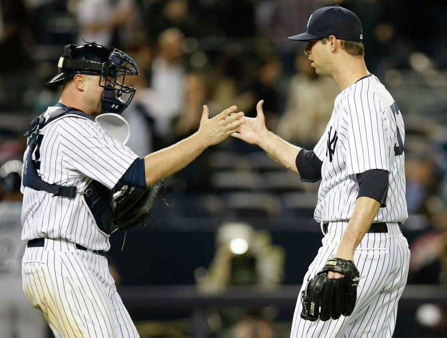 New York Yankees catcher Brian McCann, left, congratulates New York Yankees relief pitcher Chris Martin after Martin closed out the Yankees 4-2 victory over the Tampa Bay Rays in a baseball game at Yankee Stadium in New York, Tuesday, April 28, 2015.  (AP Photo/Kathy Willens) Photo: Kathy Willens, Associated Press / AP