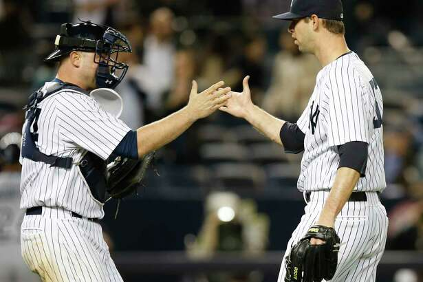 New York Yankees catcher Brian McCann, left, congratulates New York Yankees relief pitcher Chris Martin after Martin closed out the Yankees 4-2 victory over the Tampa Bay Rays in a baseball game at Yankee Stadium in New York, Tuesday, April 28, 2015.  (AP Photo/Kathy Willens)