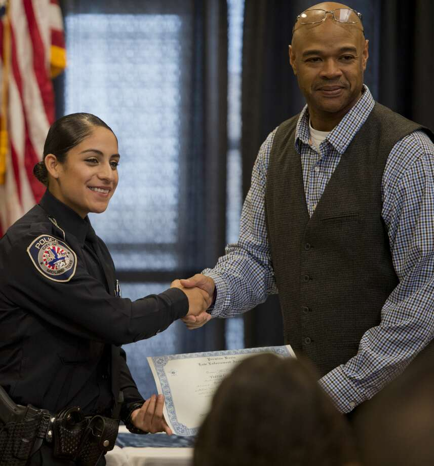 Yvette Gonzales receives her graduation certificate from Terrence Sommers, Permian Basin Law Enforcement Academy coordinator, 12/11/17 during the graduation ceremony at the Midland Horseshoe. Tim Fischer/Reporter-Telegram Photo: Tim Fischer/Midland Reporter-Telegram