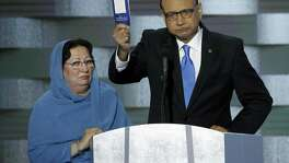 Khizr Khan holds a copy of the U.S. Constitution during the last day of the Democratic National Convention last year in Philadelphia. Khizr and Ghazala Khan, standing beside him, are members of a Gold Star family. President Trump would do well to read the Constitution.