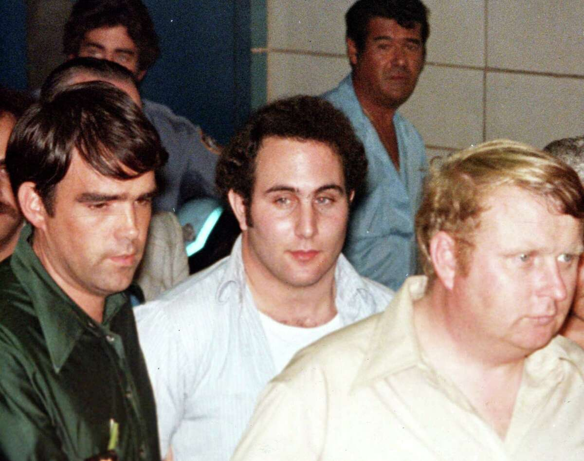 FILE--Police officials surround David Berkowitz, 24, of Yonkers, N.Y., outside Brooklyn's 84th precinct after his arrest as the 'Son of Sam' killer in this August 11, 1977 file photo. Berkowitz says he is saddened by the upcoming release of Spike Lee's movie based on his 1977 murder spree. 'This madness, the ugliness of the past is resurfacing again _ all because some people want to make some money,' Berkowitz said in a prison interview with The New York Times published Sunday, June 20, 1999.